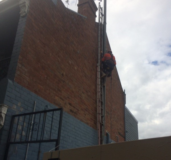 Man using ladder going to the roof